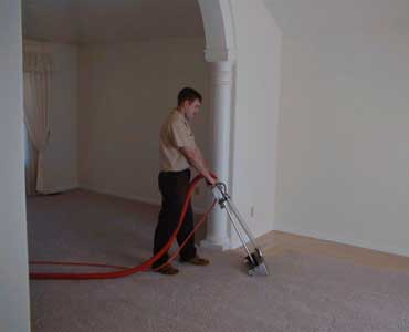 the carpet cleaning technician is using the washer on the carpet